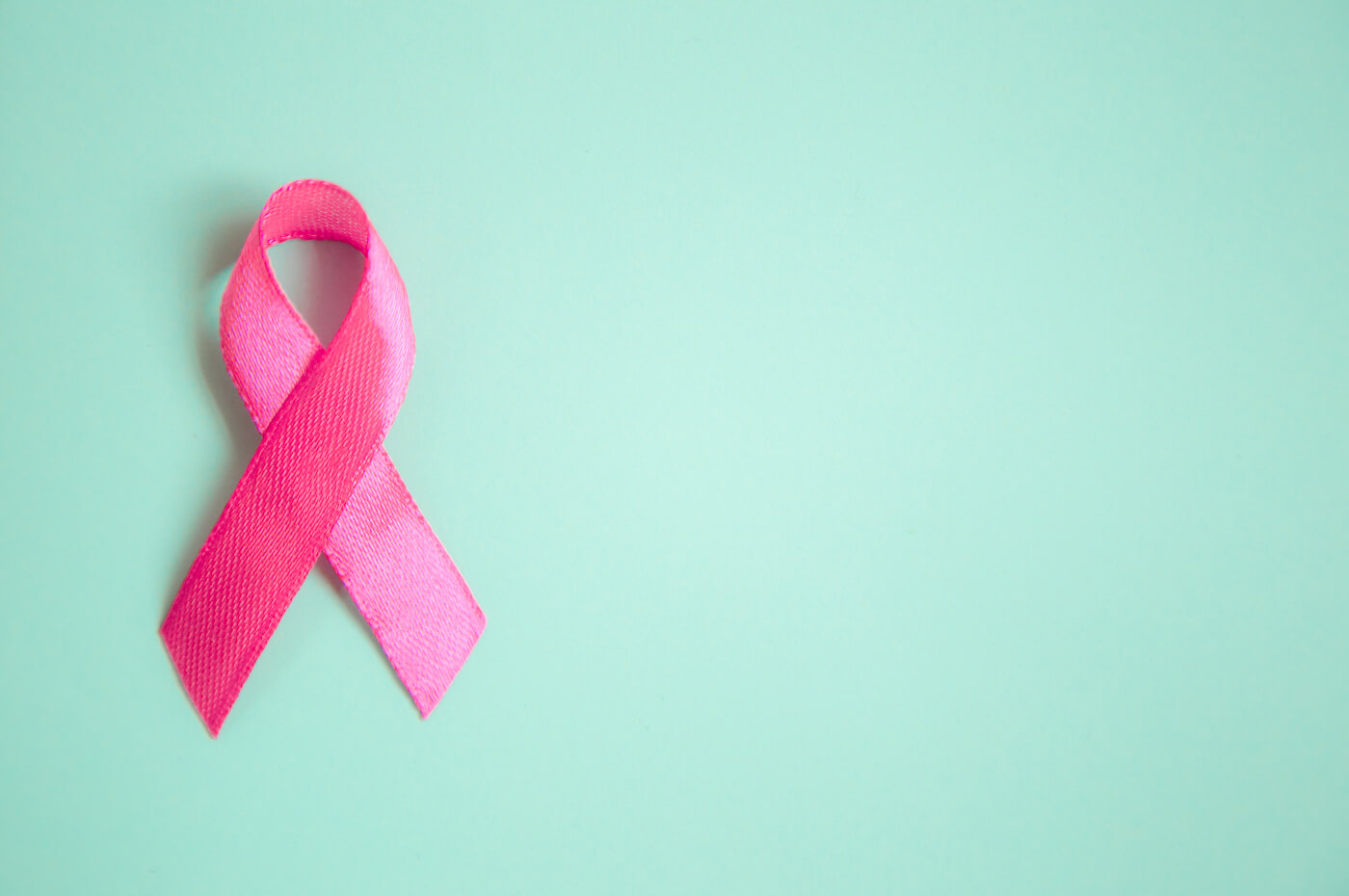 Pink Breast Cancer Awareness ribbon on green background
