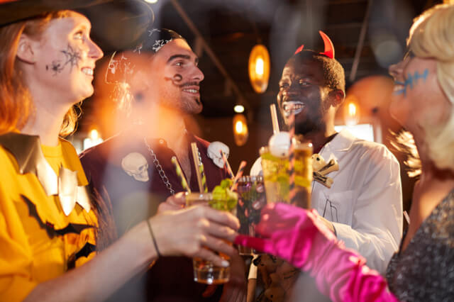 Four adults at Halloween party drinking cocktails