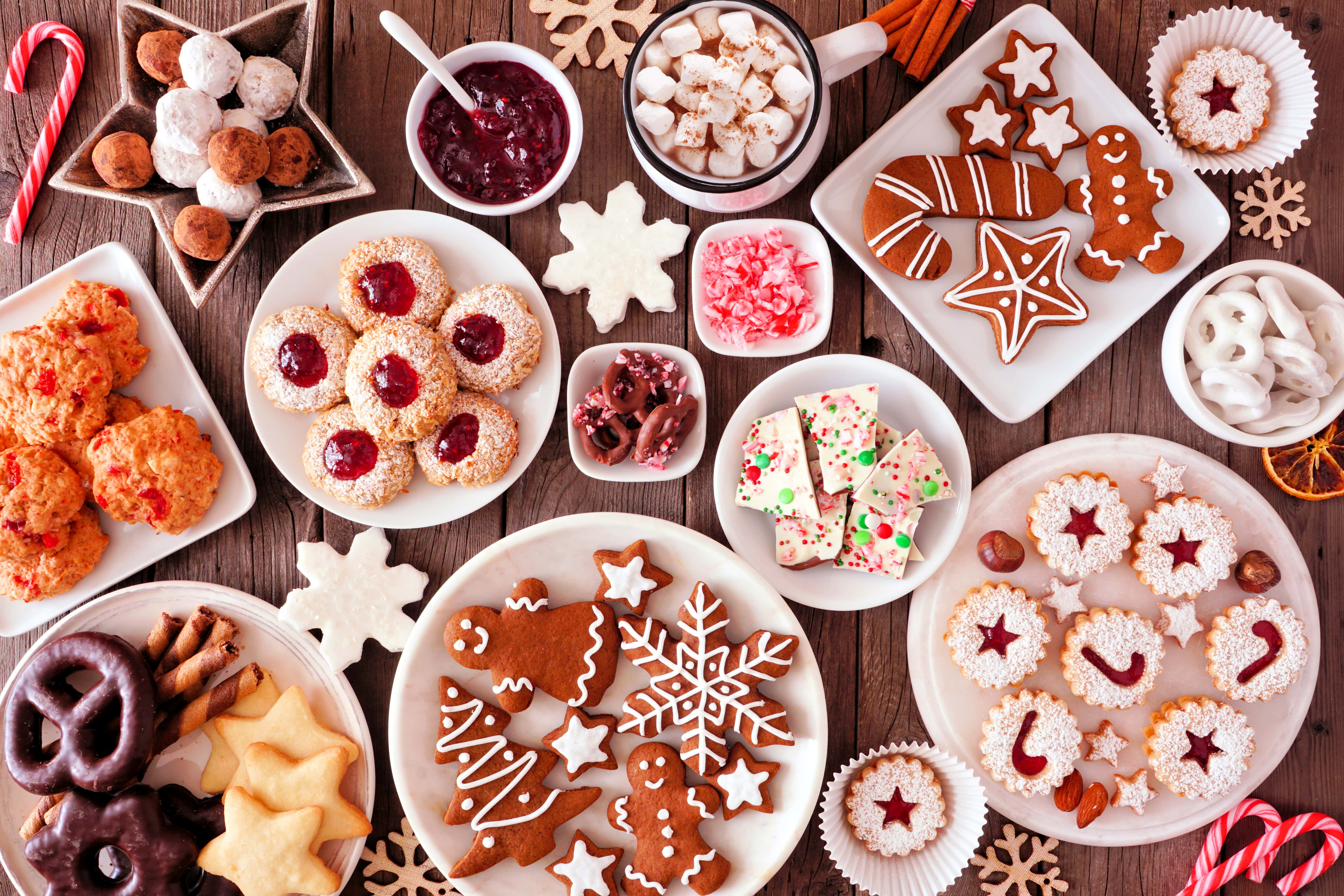 Christmas-baking-table-scene-with-assorted-sweets-and-cookies,-top-view-over-a-rustic-wood-background
