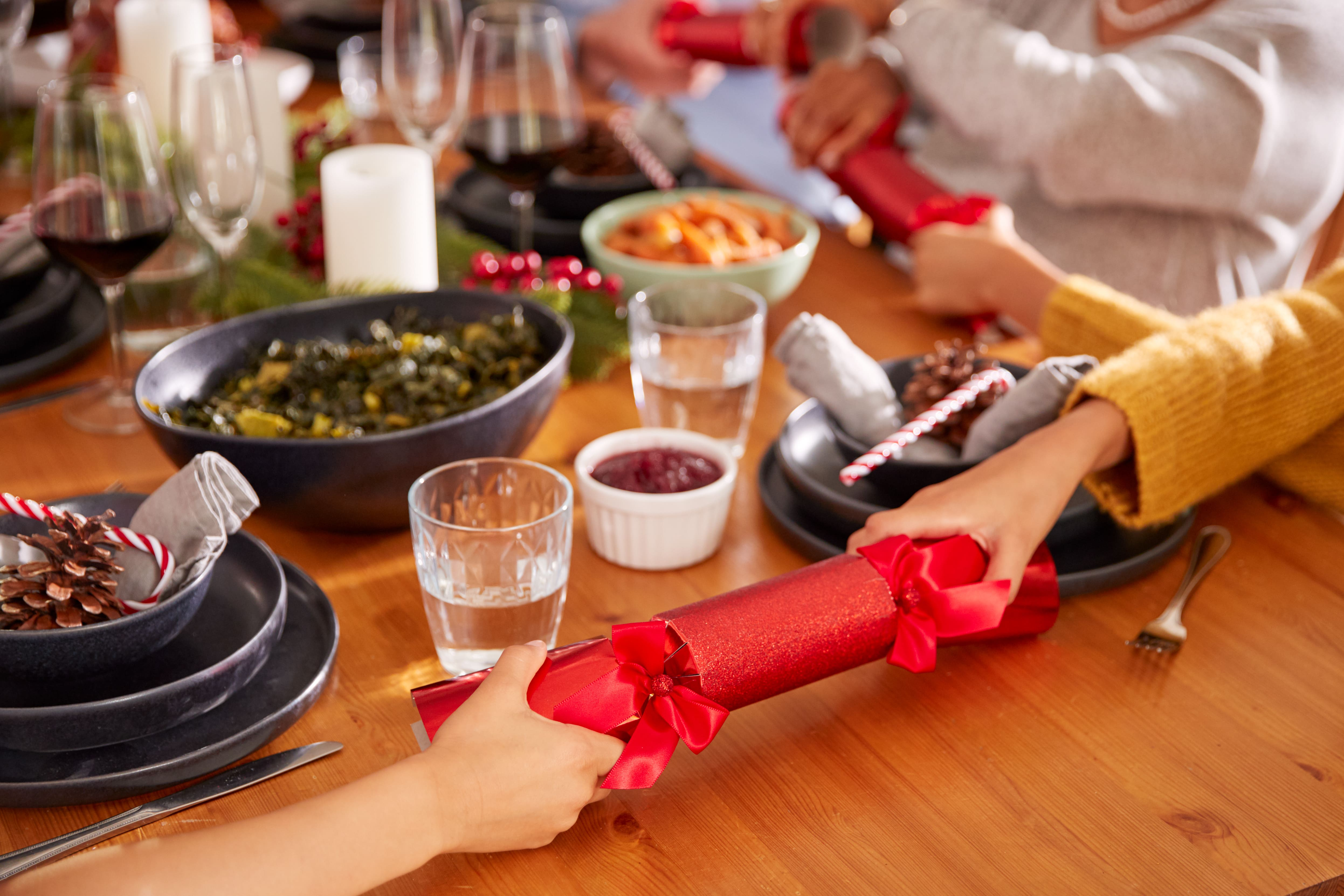 Close-Up-Of-Multi-Generation-Family-Pulling-Christmas-Crackers-As-They-Sit-For-Meal-At-Table