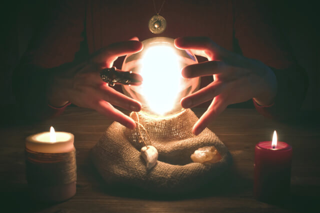 crystal-ball-illuminated-in-seance-with-hands-and-candles-either-side