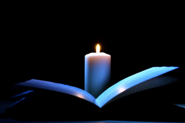 open-book-lit-by-candlelight-in-the-dark