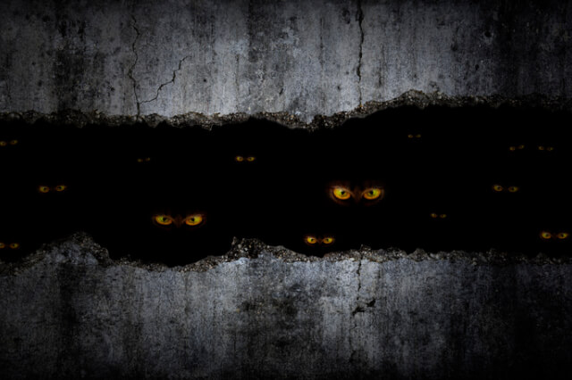 scary-eyes-between-grungy-cracked-and-broken-concrete-wall-in-the-dark